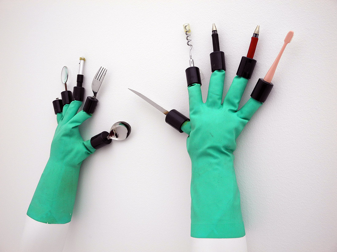 a pair of chindogu gloves with tools on the end of each finger