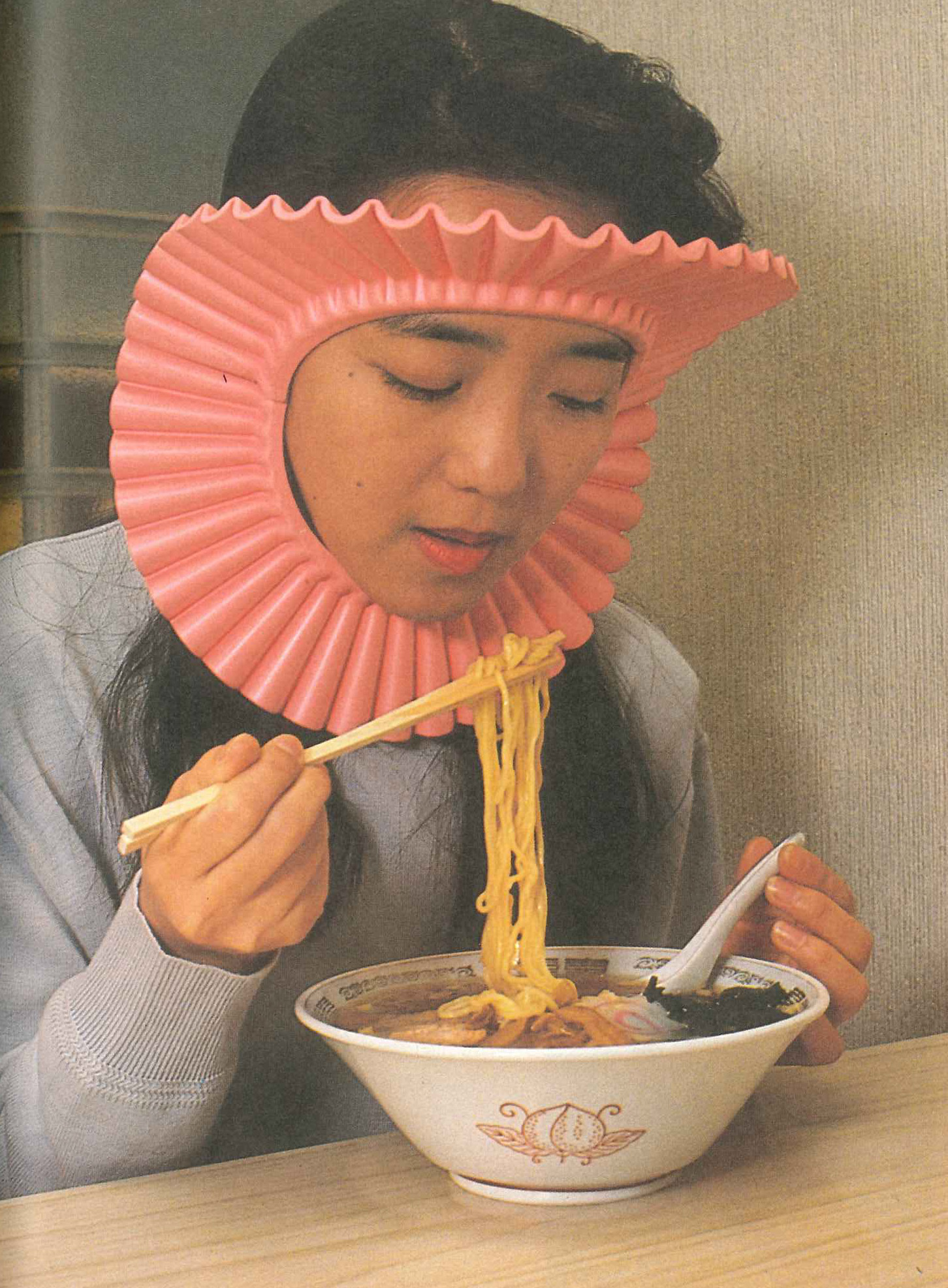 woman eating noodles wearing chindogu