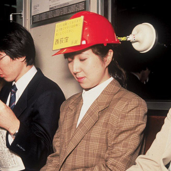 woman wearing hard hat with plunger attached