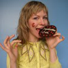 A blond woman eating a cookie
