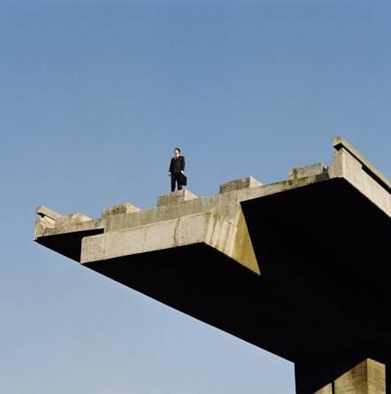 man standing on overpass bridge