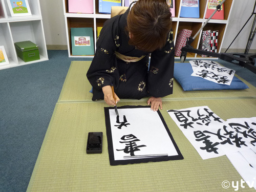 woman kneeling practicing kanji