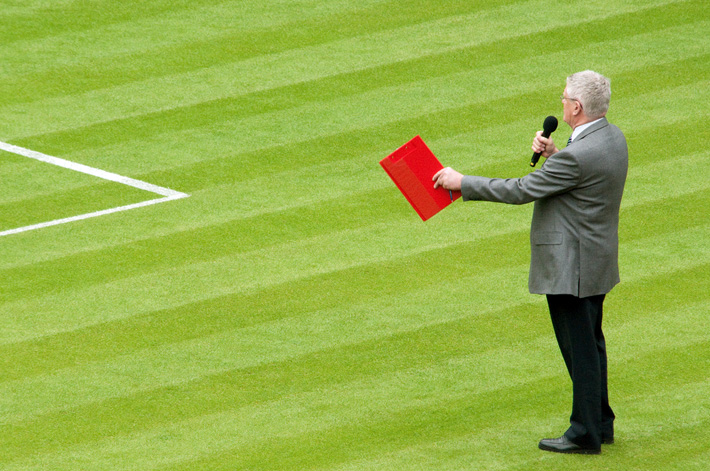 man on football field with microphone and red folder
