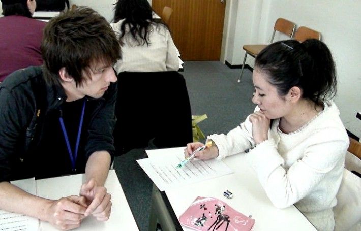 A caucasian student speaking with a Japanese person
