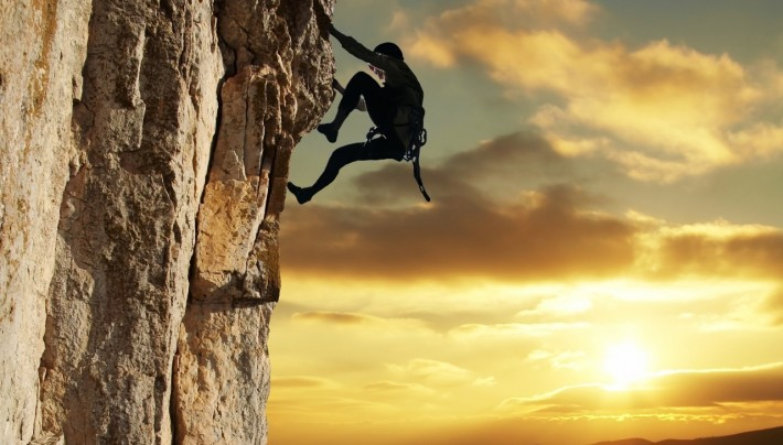 Rock climber silouhetted against the sun