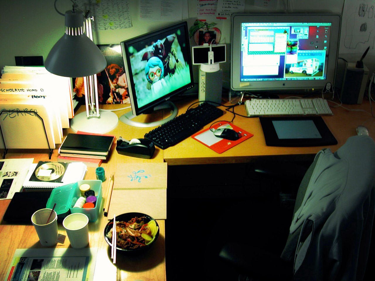 a workspace with two monitors and some food