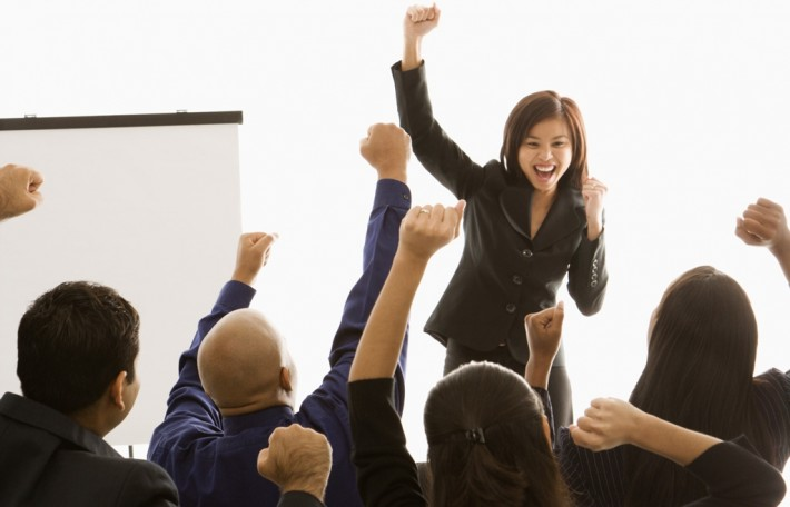 People in a meeting holding their fists up in the air