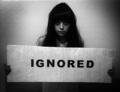"A girl holding an ""IGNORED"" sign"