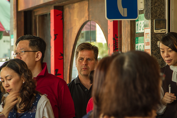 white male standing under a phone sign in taiwan