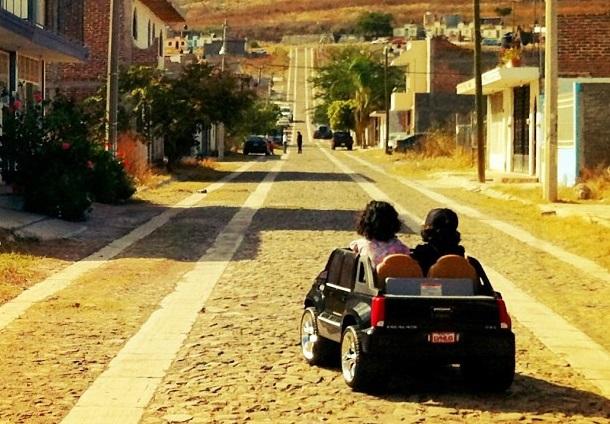 children riding in toy car