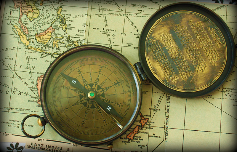 An old compass resting on a map