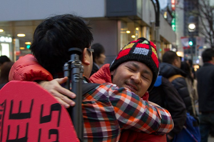 Two Japanese photographers sharing a hug