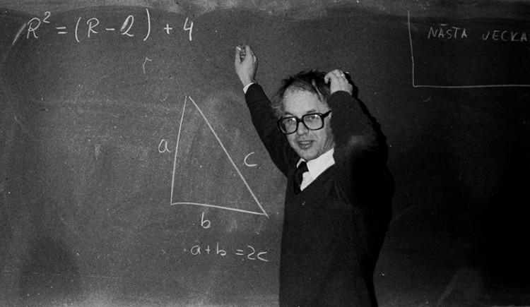 A math teacher writing a problem on a blackboard