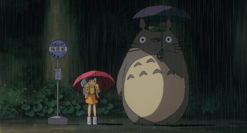 Girls and Totoro standing in the rain by a bus stop
