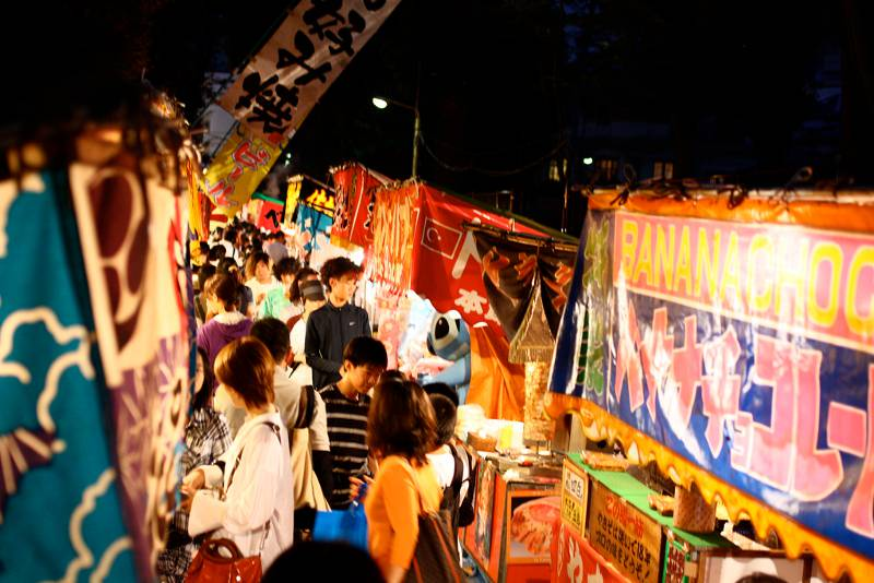 A row of food booths at a Japanese festival