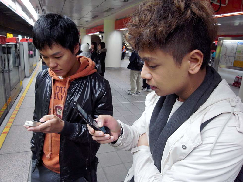 Two men looking at their cell phones