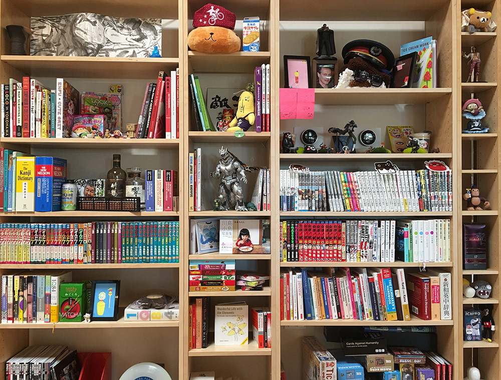crowded bookcase filled with books about japan