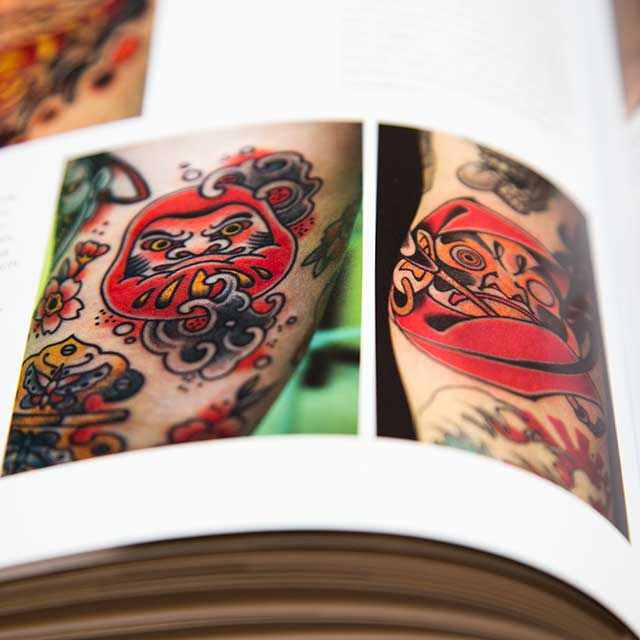 two daruma tattoos in a book