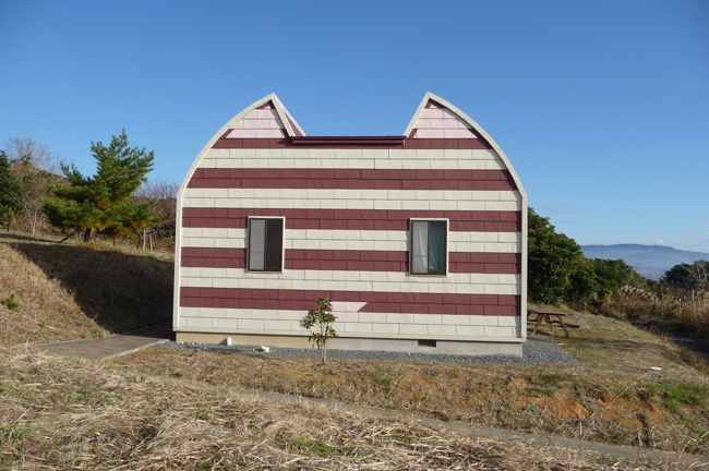 house shaped like cat with red and white siding