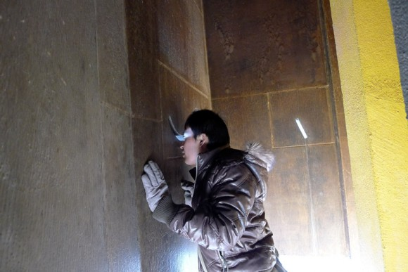 man looking through slit in wall