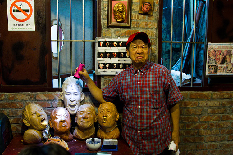 guy making a face next to a pile of heads