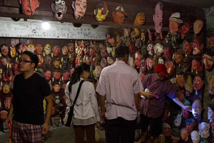 people exploring a room full of masks