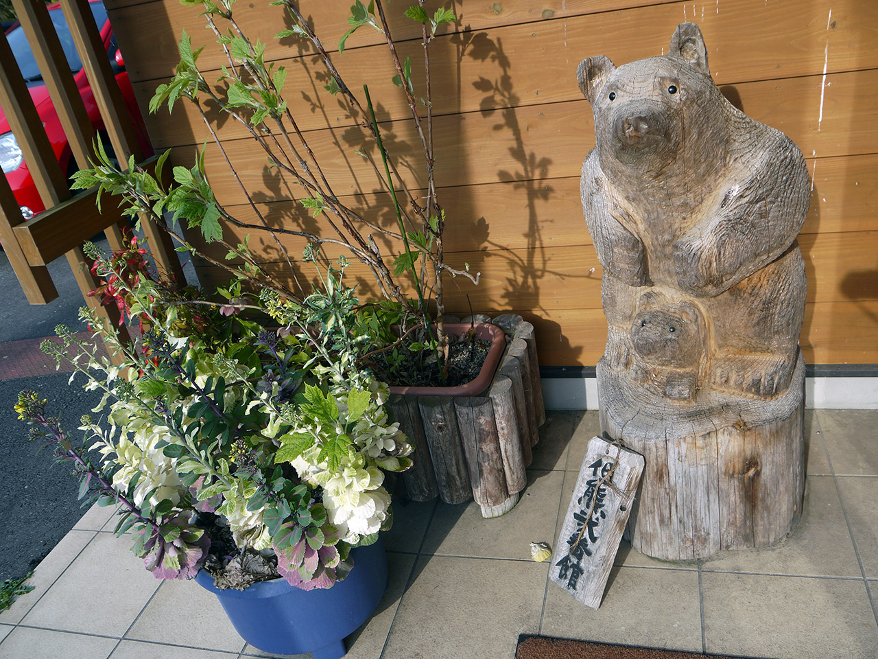 wooden bear statue next to some plants