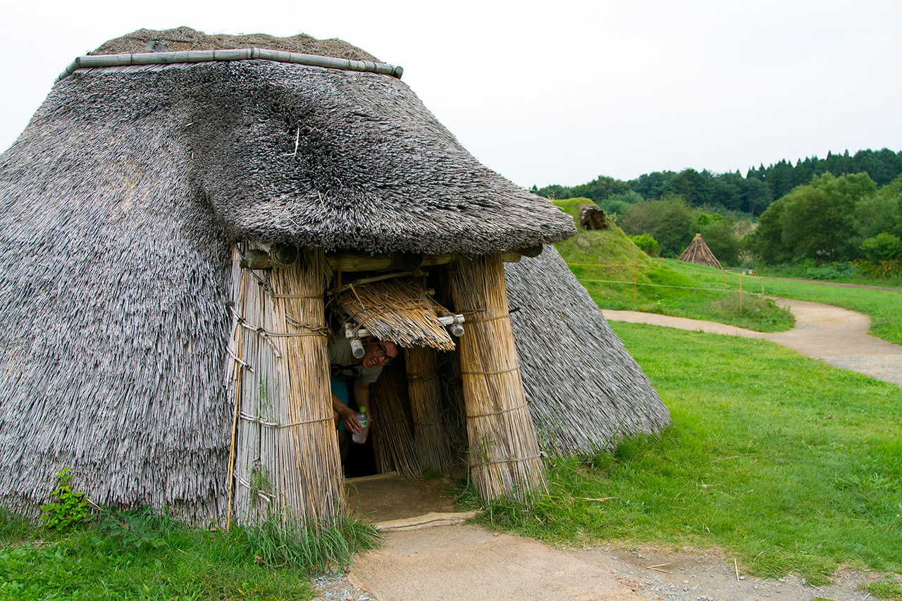 man poking head out from inside japanese historic hut