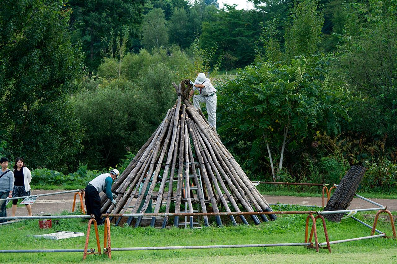onlookers watch two men build hut