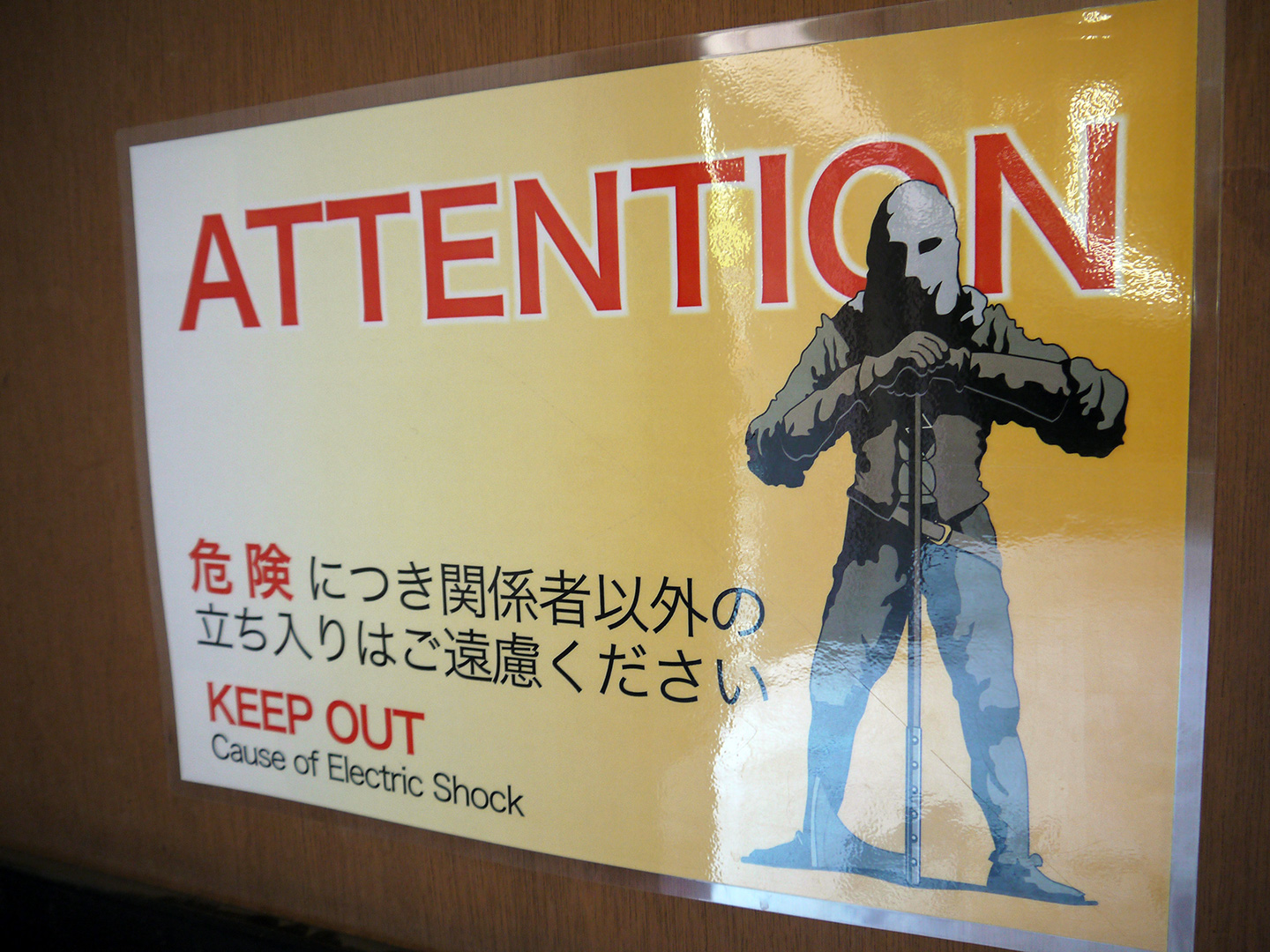 warning sign with picture of menacing hooded man