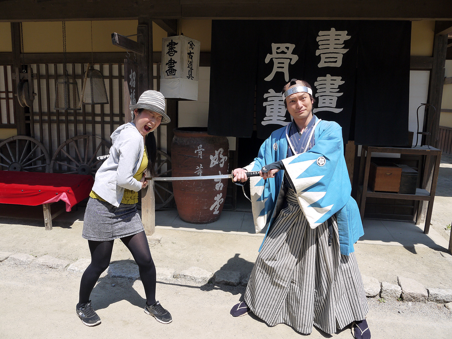 samurai pretends to stab woman with his sword