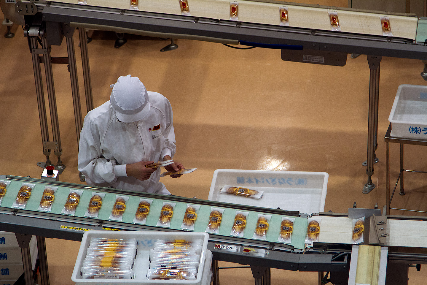 worker inspecting unagi pies on the assembly line