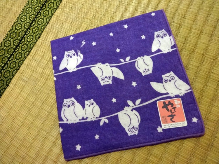cloth featuring white cartoon fukuro on purple background
