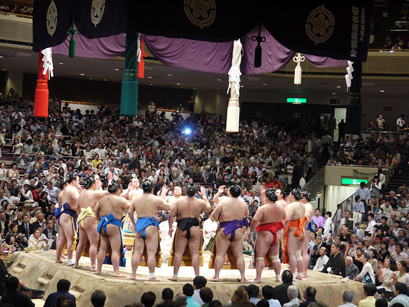 sumo wrestlers in a circle facing each other