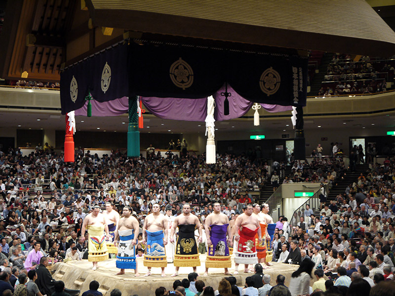circle of sumo wrestlers facing the crowd