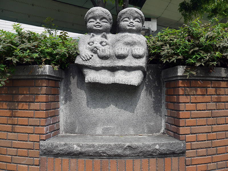 Statue of two girls with a cat nestled in them