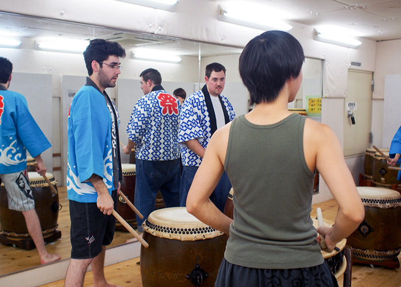 foreigners in a circle learning taiko in japan