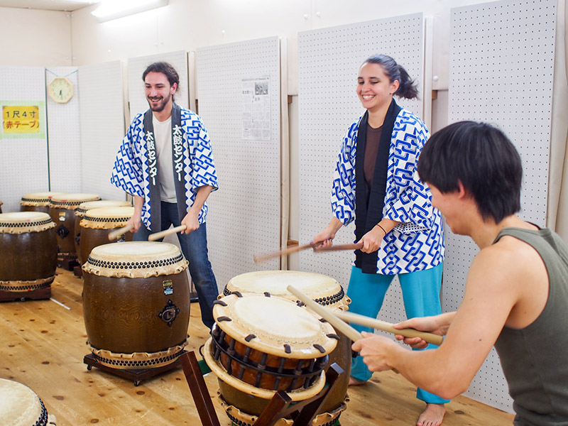 two foreigners learning taiko japanese drums in kyoto
