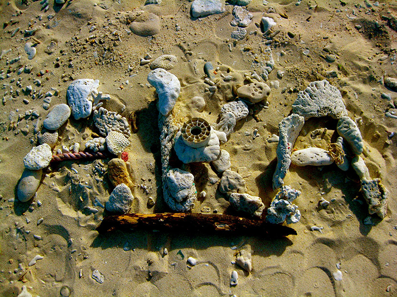aka letters in sand formed with seashells and beach paraphernalia