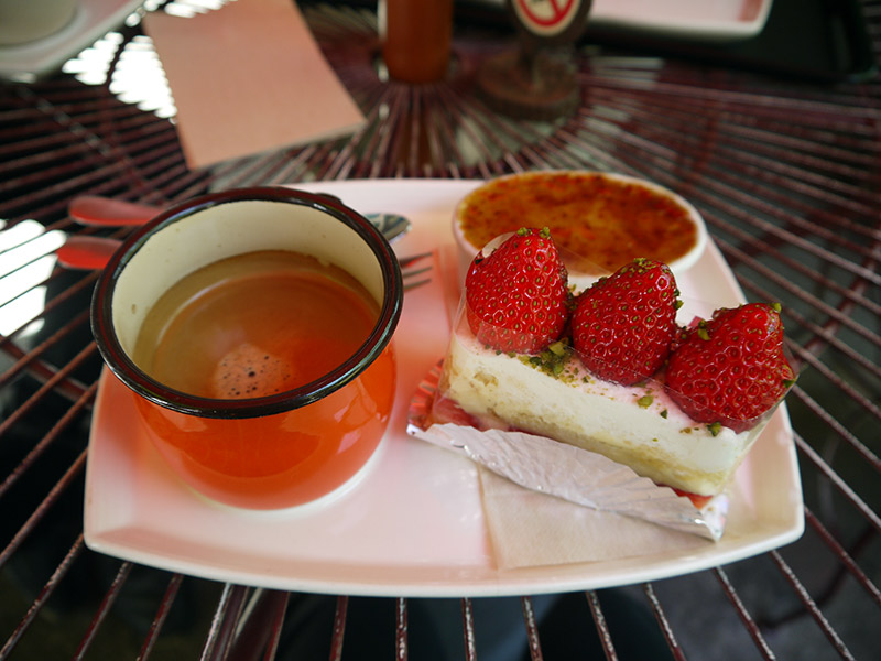 strawberry shortcake rectangle and red cup of coffee at cake shop