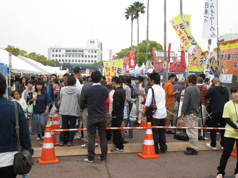 people stnading in line for food japan orange cones