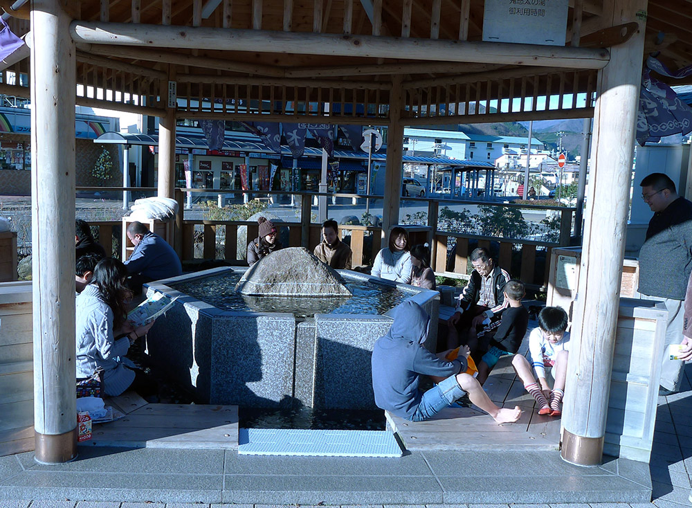 people at a foot onsen in japan