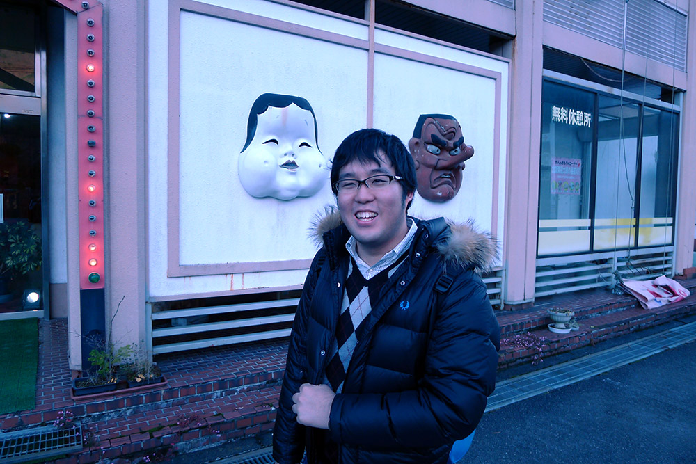 man standing smiling in front of a building with japanese masks