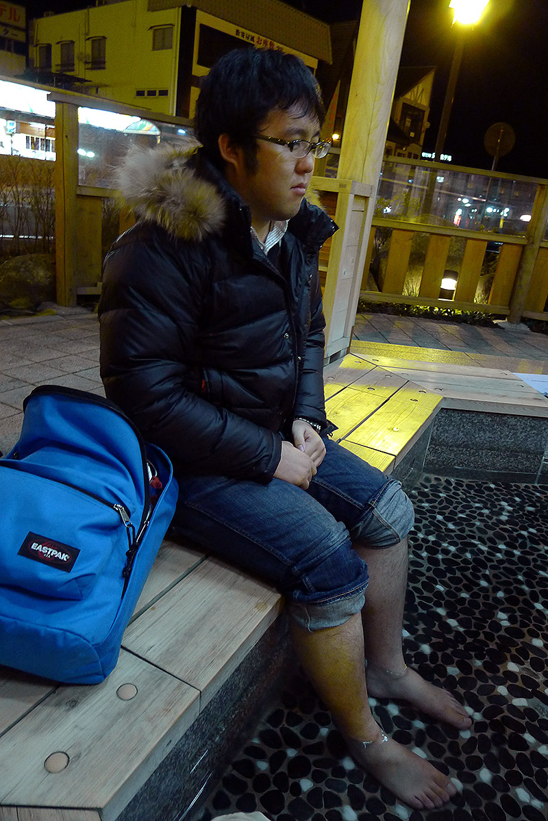 man in a foot onsen looking despondent