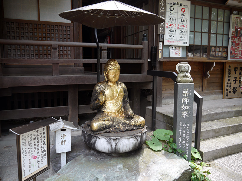 japanese shrine statue of the buddha covered in gold leaf