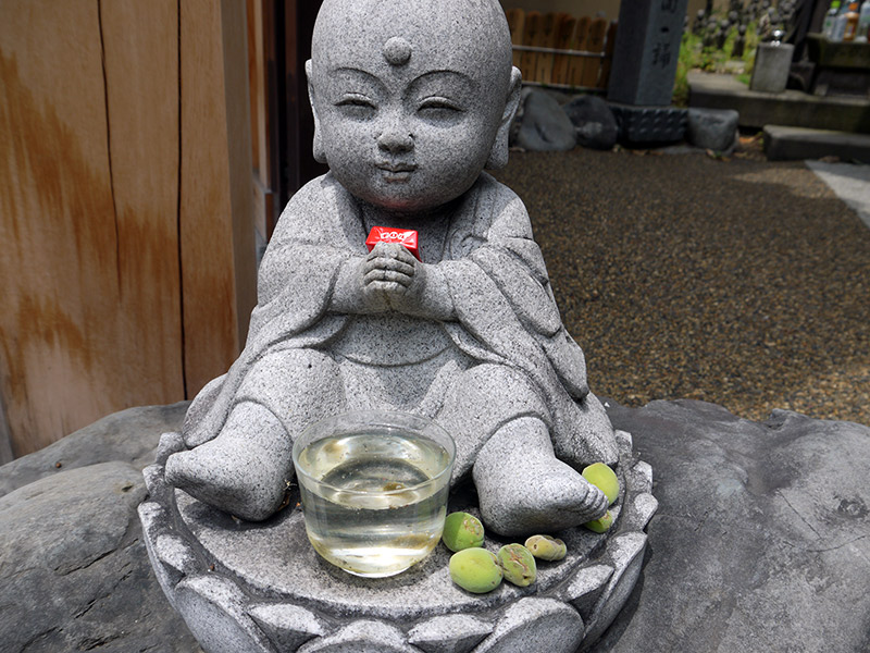 japanese stone shrine statue jizo with chocolate and plums