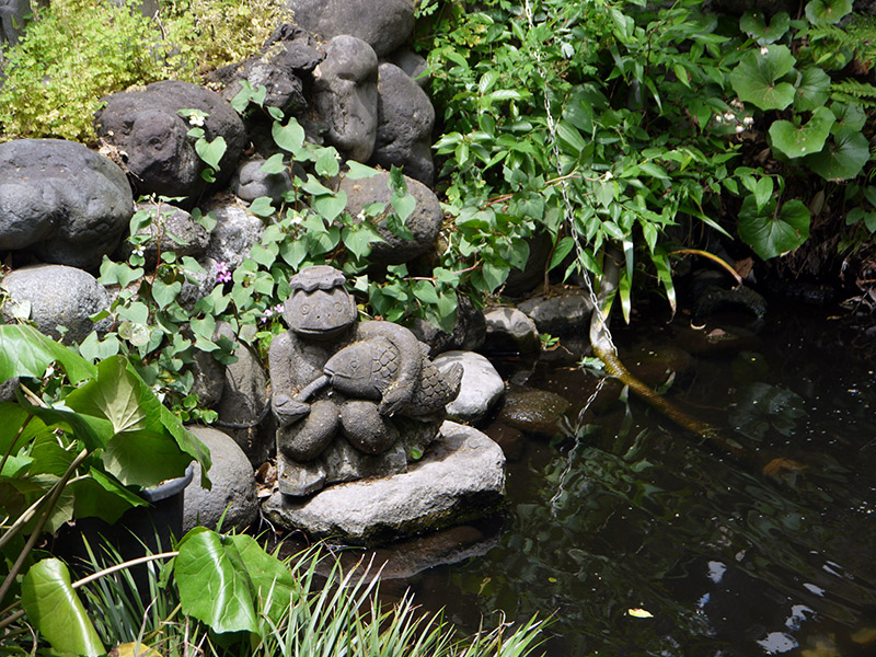 small stone sculpture in a pond garden