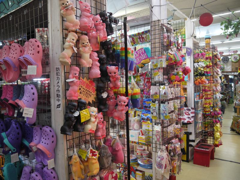 pink crocs and plastic pink kittens hanging in a store
