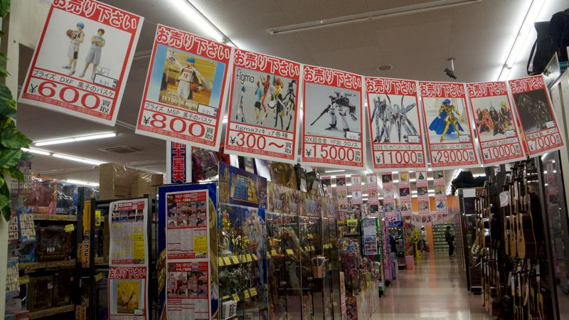 signs advertising japanese toys cartoons manga in a store