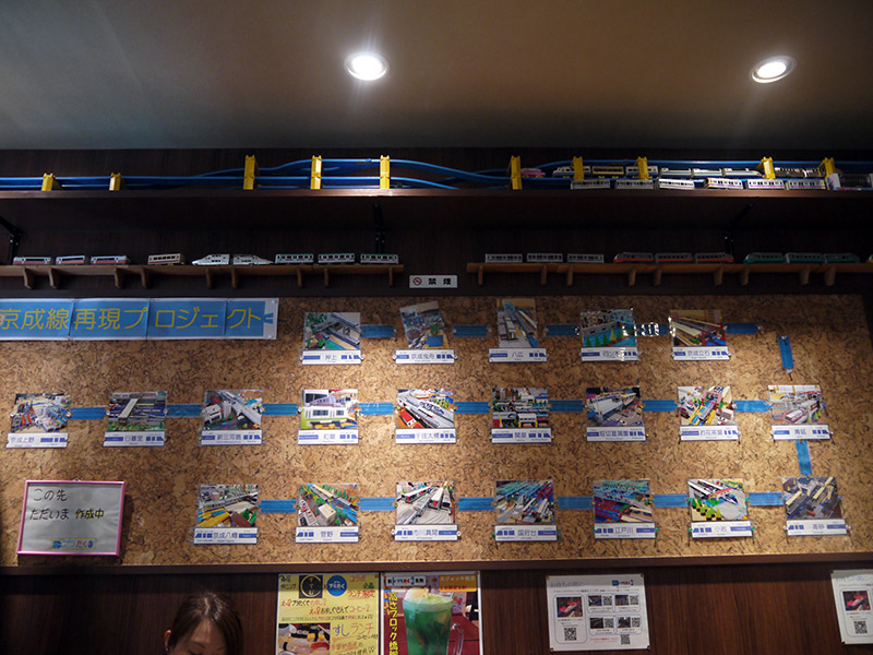 A bulletin board with various Plarail train models